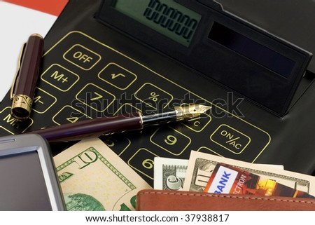 Calculator, credit card, cash, gold?n pen and cell phone on a business workplace