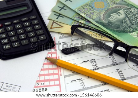calculator, glasses, pencil and polish money banknotes on bills