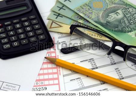 calculator, glasses, pencil and polish money banknotes on bills - stock photo