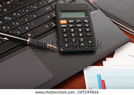 Calculator, laptop and financial documents on the table - stock photo