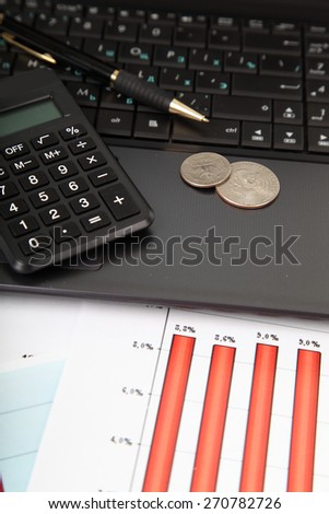 Calculator, laptop and money on the table - stock photo
