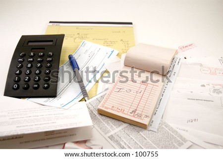 Calculator, legal pad, receipt book, paycheck and a pile of bills
