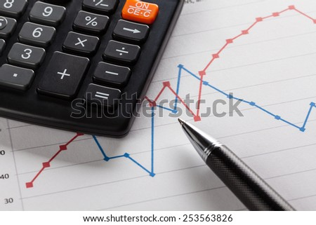 calculator lies with the sheet business graphs. pen