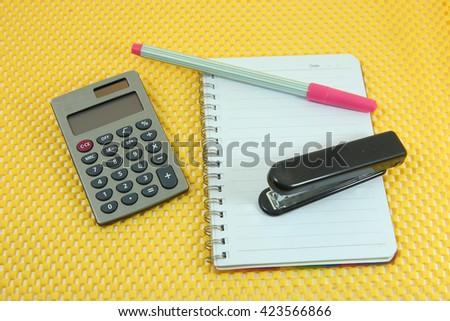 Calculator ,note book, pink pen and black  stapler on yellow background - stock photo