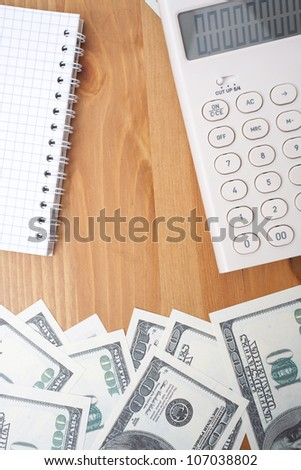 Calculator, notebook and dollars on the table - stock photo