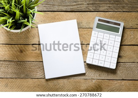 Calculator, notepad and green plant. Calculator, notepad and green plant on wooden background - stock photo
