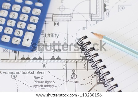 Calculator, Notepad And Pencil Arranged On House Plans - stock photo