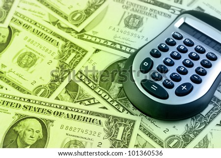 Calculator on American banknotes - stock photo