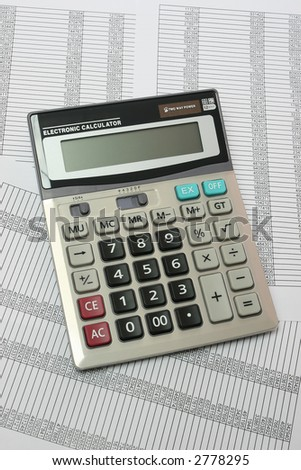 calculator on background with tables - stock photo