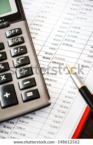 Calculator on financial and business documents - stock photo