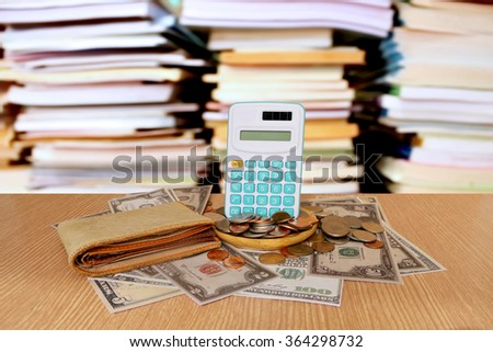calculator on pile of banknote with blur stacking book background - stock photo