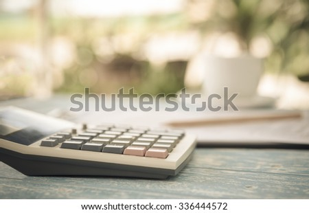 Calculator on the table in the backyard. finance,account,economy at home concepts. vintage style. - stock photo