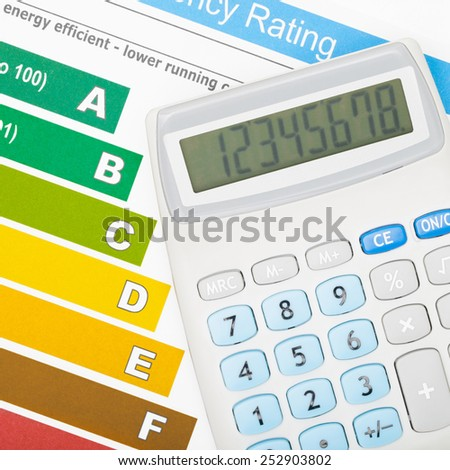 Calculator over colorful energy efficiency chart - stock photo