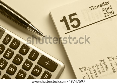 Calculator, pen and calendar that was turned to April 15th, the Tax day in the United States.