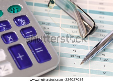 Calculator, pen and eyeglasses on paper - stock photo