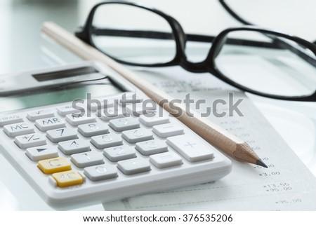 Calculator pen and glasses - stock photo