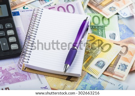 Calculator pen money and notebook on a banknotes background