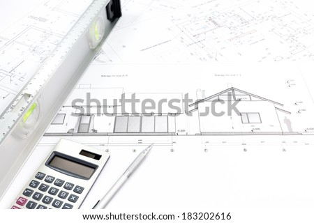 Calculator, pencil, spirit level and architectural plans of modern house