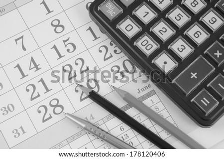 Calculator, pencils and silver pen on calendar - stock photo