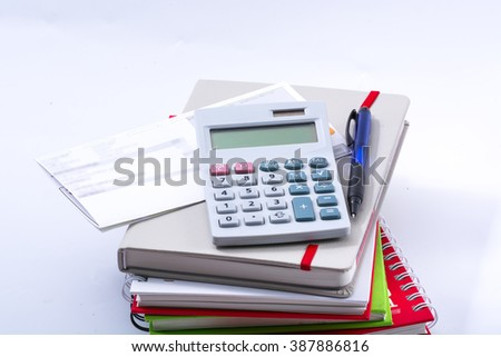 Calculator put on a pack of books. - stock photo
