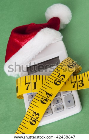 Calculator with a Santa Hat squeezed by a measuring tape representing a tight holiday budget. - stock photo