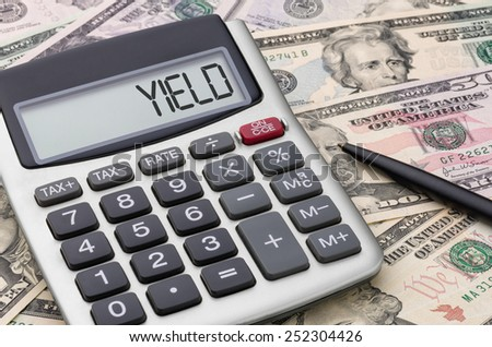 Calculator with money - Yield - stock photo