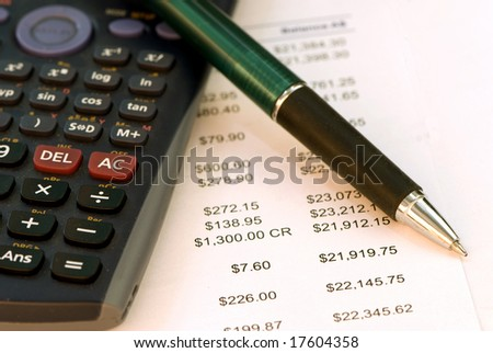 Calculator with pen and tax sheet underneath