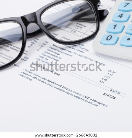 Calculator with pen, glasses and utility bill under it - close up shot - stock photo