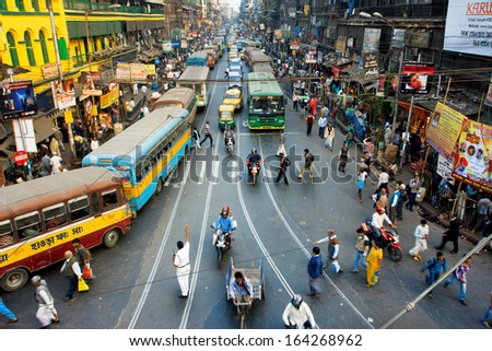 CALCUTTA, INDIA - JAN 18: Pedestrians cross the road in front of motorcycles, cars and buses at the crossroads on January 18, 2013 in India. Kolkata has a density of 814.80 vehicles per km road length - stock photo