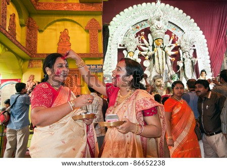 CALCUTTA - OCTOBER 6: Married Bengali Hindu women smear and play with vermilion during Sindur Khela traditional ceremony on the final day of Durga Puja festival on October 6, 2011 in Calcutta, India.