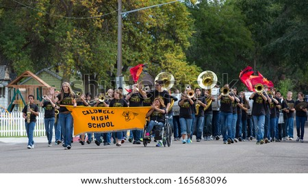 CALDWELL, IDAHO/USA - SEPTEMBER 27: A Group of students start the parade playing music and carry a banner at the Caldwell High School Homecoming parade on September 27, 2013  - stock photo