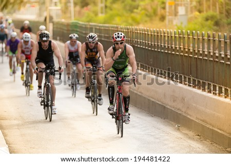 CALELLA, SPAIN MAY 18:  Triathletes ride speed cycle on the Ironman triathlon competition at Calella beach, May 18, 2014 in Calella, Spain - stock photo