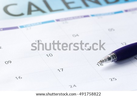 calendar and a blue pen to mark the desired date