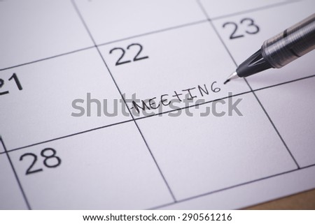 Calendar marked by a pen with the word written meeting - stock photo