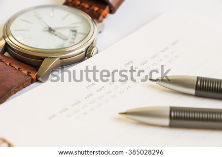 Calendar notebook with pen, pencil and vintage watch, selective focus - stock photo