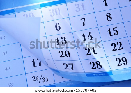 Calendar showing the month and individual days with the corner flipped up to reveal part of the month below - stock photo