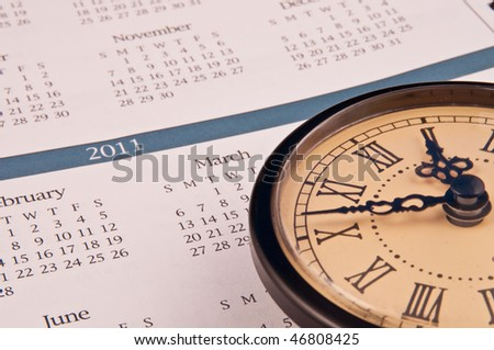 Calendar with clock sporting roman numerals on top