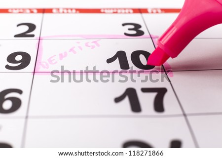 Calendar with dentist appointment on the 10-th highlighted with pink marker - stock photo