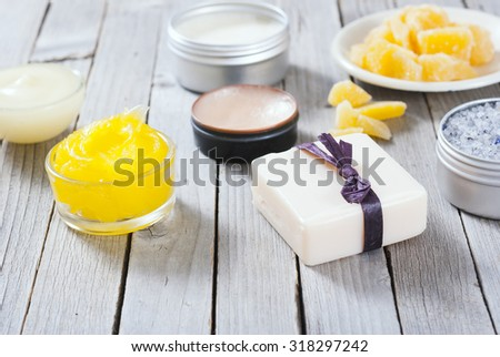 Calendula cream, lip balm, raw bees wax, bath salt soap and other cosmetics on rusty wood table