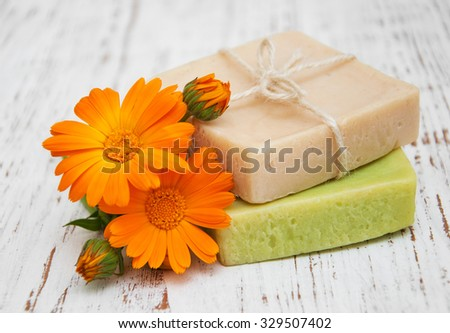 calendula flowers  and handmade bath soap on a wooden background