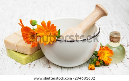 calendula flowers in mortar and handmade bath soap on a wooden background - stock photo