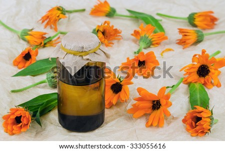 Calendula marigold flowers with oil, covered on with parchment paper - stock photo