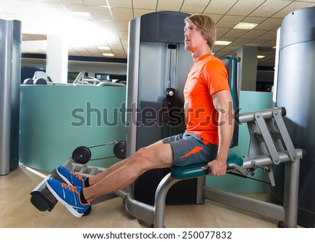 Calf extension blond man at gym exercise machine workout indoor - stock photo