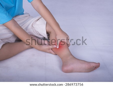 Calf leg pain, child holding sore and painful muscle, sprain or cramp ache filled with red bright place. Person injured when exercising or playing. - stock photo