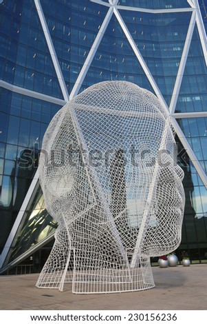 CALGARY, CANADA - JULY 29:  Wonderland sculpture by  Jaume Plensa in the front of the Bow Tower on July 29, 2014 in Calgary, Alberta, Canada. Jaume Plensa is a Catalan Spanish artist and sculptor - stock photo
