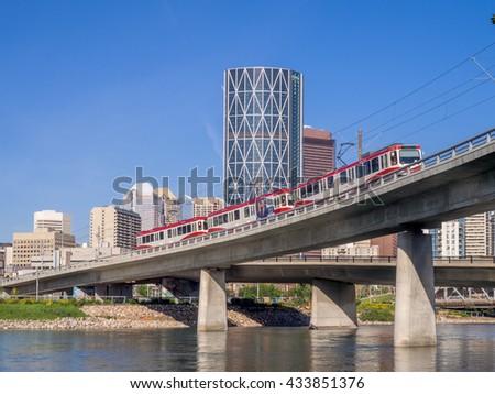 CALGARY, CANADA - JUNE 5: C-train crossing the Bow River on June 5, 2016 in Calgary, Alberta Canada. The C-Train is Calgary's main light rail transit system.  - stock photo
