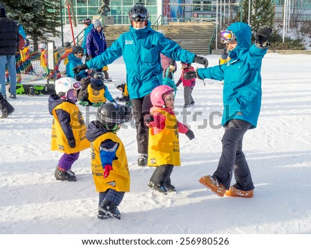 CALGARY, CANADA - MAR 1: Kids learning to ski at Canada Olympic Park om March 1, 2015 in Calgary, Alberta Canada.  Visible are toddlers in a pre-school skiing class.   - stock photo