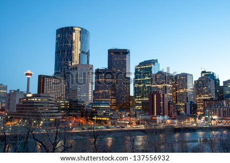 Calgary skyline at dusk, with Bow River in foreground. - stock photo
