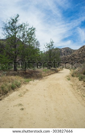 California dirt road leads through meadow into Angeles Mountains. - stock photo