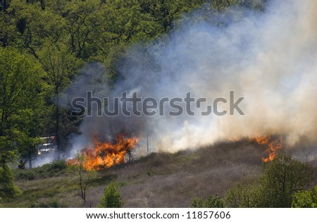 California Firefighter battling a wildfire quickly raging across a field. - stock photo